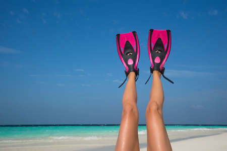 snorkelling: Woman relaxing on summer beach vacation holidays lying in sand. Flippers in legs. Diver fins