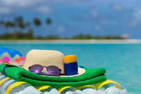 Sunglasses and straw hat on a air mattress in sea. Tropical summer concept. Stock Photo