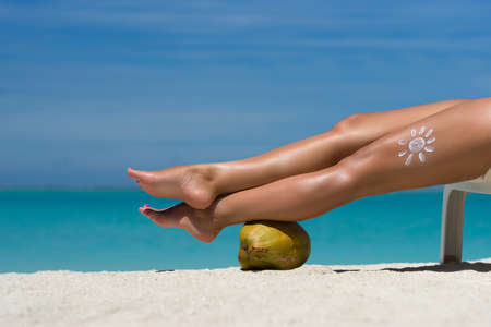 Womens beautiful legs on coconut on the beach, blue sea background Stock Photo