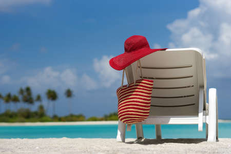 Beach chairs with hat on white sandy beach Stock Photo