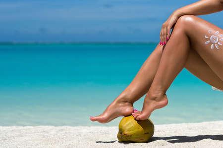 Women's beautiful legs on coconut on the beach, blue sea background