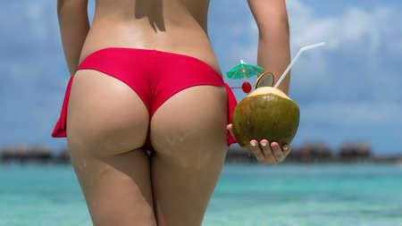 Close up fille de retour en bikini contre plage de l'océan et la noix de coco