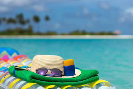 lilo: Sunglasses and straw hat on a air mattress in sea. Tropical summer concept. Stock Photo