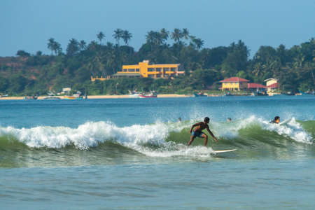 surfers paradise: WELIGAMA, SRI LANKA - JANUARY 09 2017: Unidentified man surfing on a large wave on Weligama beach on the coast of Indian ocean  - is the best surf paradise in Sri Lanka