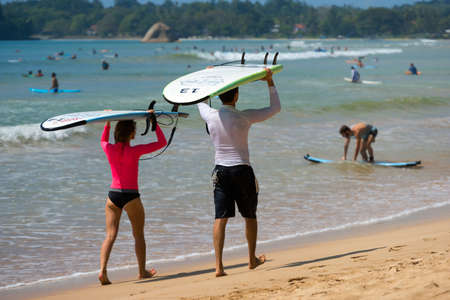 surfers paradise: WELIGAMA, SRI LANKA - JANUARY 09 2017: Unidentified couple surfing on a large wave on Weligama beach on the coast of Indian ocean  - is the best surf paradise in Sri Lanka