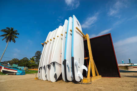 WELIGAMA, SRI LANKA - JANUARY 12 2017: Set of different color surf boards in a stack by ocean.WELIGAMA, SRI LANKA. Surf boards on sandy Weligama beach. On Weligama beach surf is available all year around for beginner and advanced.