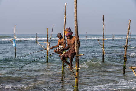 stilt: WELIGAMA, SRI LANKA - JANUARY 11 2017: Unidentified local fishermen are fishing in unique style. This type of fishing is traditional for Sri Lanka in Indian ocean. Editorial