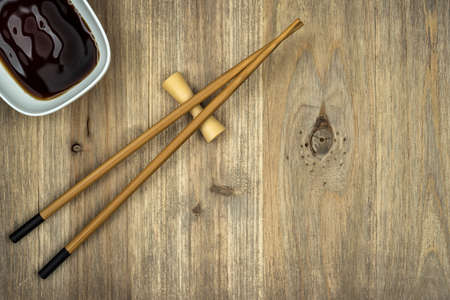 chopsticks and soy sauce on wooden table background with copy space
