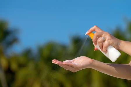 Woman hands putting sunscreen from a suncream bottle Stock Photo