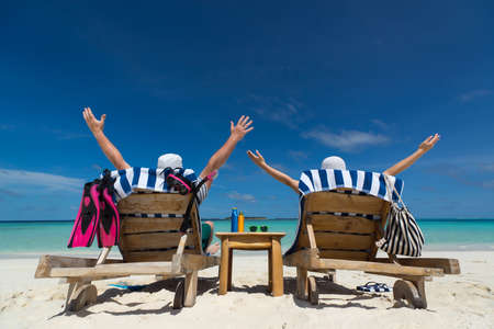 chairs: Couple on the beach at tropical resort Travel concept