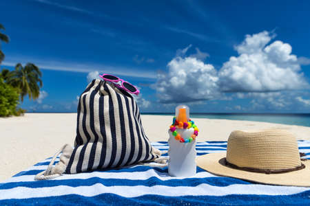 Sunscreen, hat and sunglasses on tropical beach Stock Photo