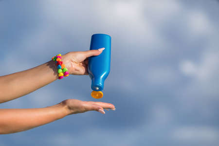 Woman hands putting sunscreen from a suncream bottle Stock Photo