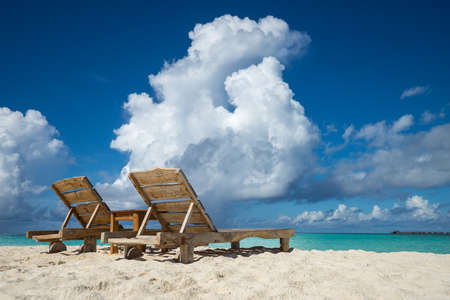 Empty wooden beach chairs on the tropical beach, vacation. Traveler dreams concept Stock Photo