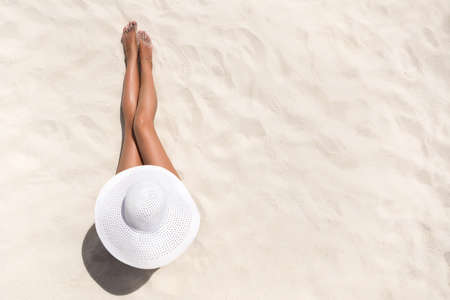 Summer holiday fashion concept - tanning woman wearing sun hat at the beach on a white sand shot from above 스톡 콘텐츠