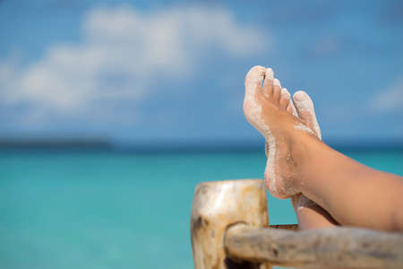 Close-up of female foot in the blue water on the tropical beach. Vacation holidays.