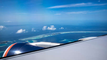 Aerial View from seaplane window over Atolls at Indian Ocean Maldives