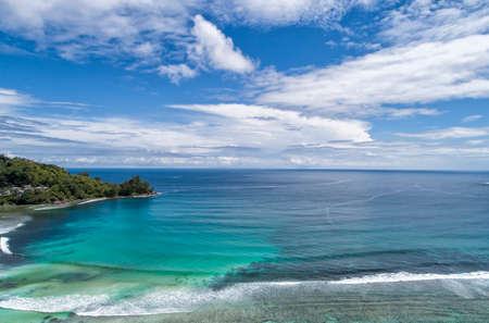 Tropical beach with sea and palm taken from drone. Beach and sea photo. Romantic beach aerial view.