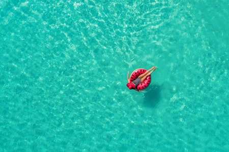 Aerial view of slim woman swimming on the swim ring  donut in the transparent turquoise sea in Seychelles. Summer seascape with girl, beautiful waves, colorful water. Top view from drone