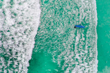 Surfers in tropical ocean waiting wave. Aerial view made with drone