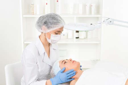 Médico esteticista con el paciente en el centro de bienestar. La cosmetóloga profesional hace el procedimiento a la hermosa chica en el gabinete de cosmetología o salón de belleza.
