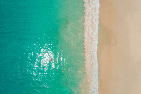 Aerial view of slim woman swimming on the swim ring donut in the transparent turquoise sea in Seychelles. Summer seascape with girl, beautiful waves, colorful water. Top view from drone Reklamní fotografie