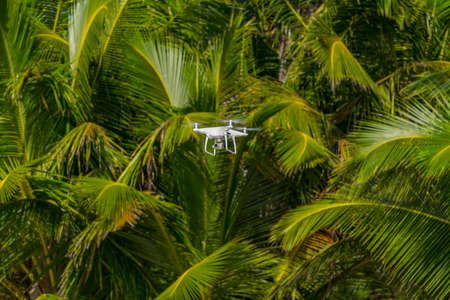 MOSCOW, RUSSIA - 2 October, 2017: a Phantom 4 Pro drone in flight, green trees in the background, selective focus on the drone. Phantom 4 Pro is a drone manufactured by the DJI company. Redactioneel