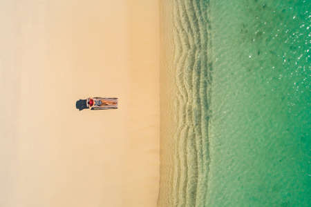 Aerial view of slim woman sunbathing lying on a beach chairin Seychelles. Summer seascape with girl, beautiful waves, colorful water. Top view from drone. Stockfoto - 126210108