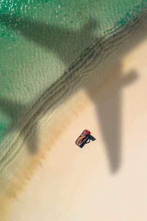 Concept of airplane travel to exotic destination with shadow of commercial airplane flying above beautiful tropical beach. Beach holidays and travel. Stockfoto - 126210172