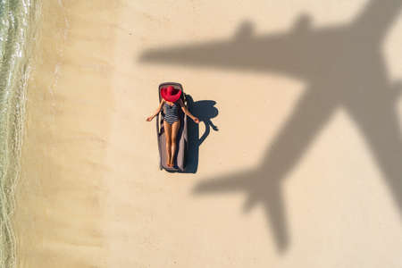 Concept of airplane travel to exotic destination with shadow of commercial airplane flying above beautiful tropical beach. Beach holidays and travel. Stockfoto