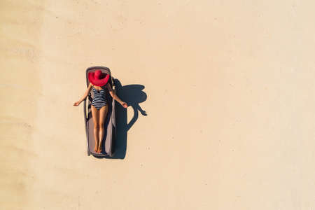 Aerial view of slim woman sunbathing lying on a beach chairin Seychelles. Summer seascape with girl, beautiful waves, colorful water. Top view from drone. Stockfoto - 126210178