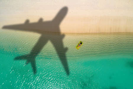 Concept of airplane travel to exotic destination with shadow of commercial airplane flying above beautiful tropical beach. Beach holidays and travel. Stockfoto - 126210180