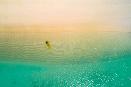 Aerial view of slim woman swimming on the swim mattress in the transparent turquoise sea in Seychelles. Summer seascape with girl, beautiful waves, colorful water. Top view from drone Stockfoto - 126210183