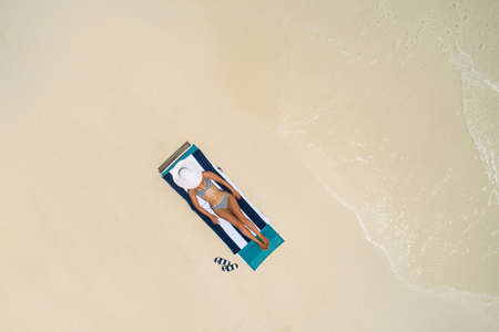 Aerial view of slim woman sunbathing lying on a beach chair in Maldives. Summer seascape with girl, beautiful waves, colorful water. Top view from drone. Stockfoto - 127762556