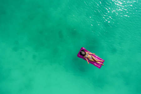Aerial view of slim woman swimming on the swim mattress in the transparent turquoise sea. Summer seascape with girl, beautiful waves, colorful water. Top view from drone Stockfoto - 127762560