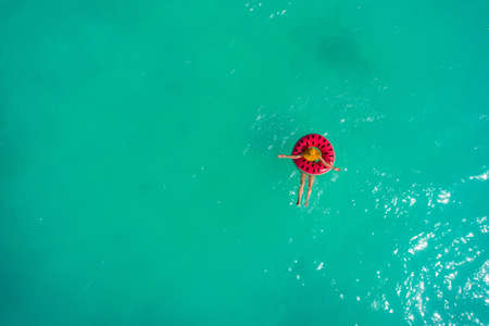 Aerial view of slim woman swimming on the swim ring  donut in the transparent turquoise sea. Summer seascape with girl, beautiful waves, colorful water. Top view from drone Stockfoto - 127762561