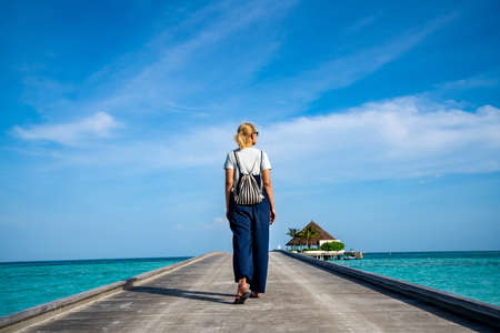 Happy woman walking along the wooden pier with blue sea and sky background Stockfoto
