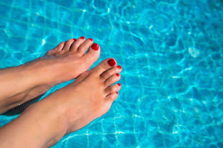Beautiful women legs in blue water. Beautiful sexy female feet relaxing by the swimming pool. Summer background for traveling.