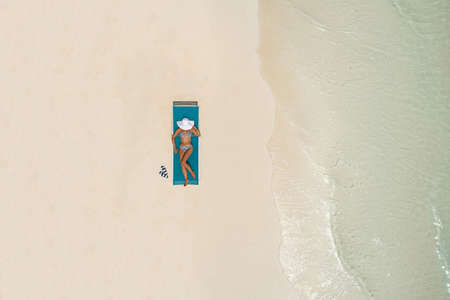 Aerial view of slim woman sunbathing lying on a beach chair in Maldives. Summer seascape with girl, beautiful waves, colorful water. Top view from drone.