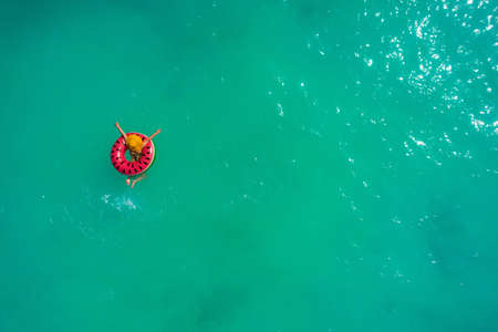 Aerial view of slim woman swimming on the swim ring  donut in the transparent turquoise sea. Summer seascape with girl, beautiful waves, colorful water. Top view from drone