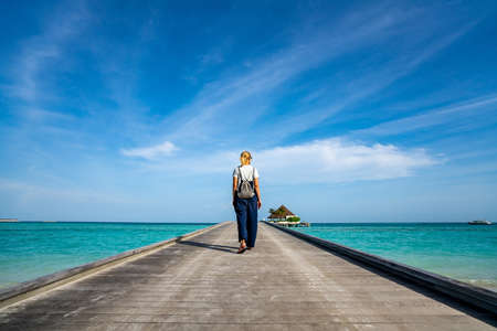 Happy woman walking along the wooden pier with blue sea and sky background 写真素材