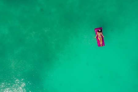 Aerial view of slim woman swimming on the swim mattress in the transparent turquoise sea. Summer seascape with girl, beautiful waves, colorful water. Top view from drone