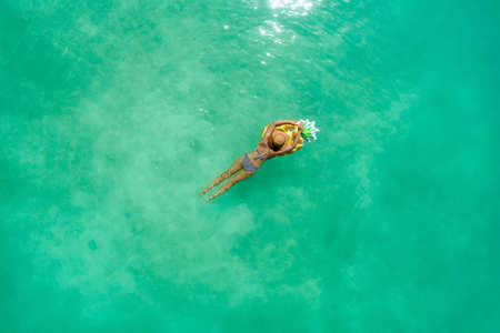 Aerial view of slim woman swimming on the transparent turquoise sea. Summer seascape with girl, beautiful waves, colorful water. Top view from drone Zdjęcie Seryjne - 131772999