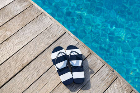 Flip flops  at the side of swimming pool, summer travel concept.