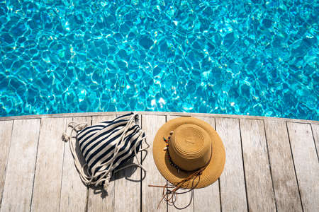 Hat at the side of swimming pool, summer travel concept  写真素材