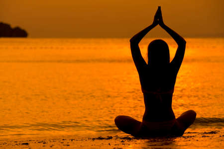 Young women meditate while doing yoga meditation, spiritual mental health practice with silhouette of lotus pose having peaceful mind relaxation on sea outdoor with sunset golden heavenly. Standard-Bild - 138038966