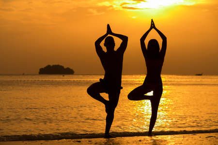 Fitness, sport and outdoor yoga concept - silhouettes of couple doing exercises on beach over sunset and sea background