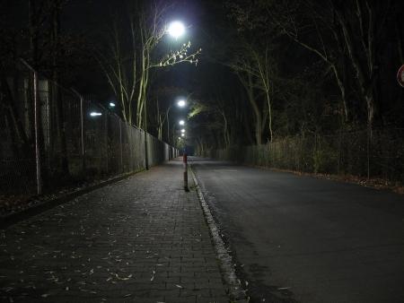 series of streetlights illuminating a deserted road photo