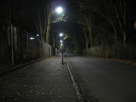 eerie: series of streetlights illuminating a deserted road