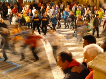 blurred people running from a black bull