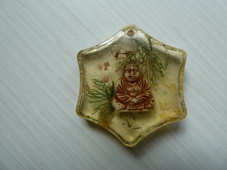 encapsulated: Tiny plastic Buddha encased in a plastic shell